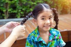 Il genitore rende a treccia i capelli asiatici del bambino al parco immagine stock