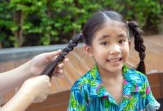 Il genitore rende a treccia i capelli asiatici del bambino al parco immagini stock
