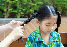 Il genitore rende a treccia i capelli asiatici del bambino al parco fotografia stock libera da diritti