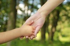 Il genitore tiene la mano di piccolo bambino fotografie stock libere da diritti