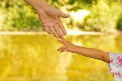 Il genitore tiene la mano di piccolo bambino fotografie stock