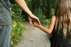 Il genitore tiene la mano di piccolo bambino fotografia stock libera da diritti