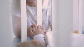 Il genitore tiene la mano di piccolo bambino che dorme in una greppia del bambino Famiglia felice ed il suo neonato insieme E video d archivio