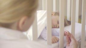 Il genitore tiene la mano di piccolo bambino che dorme in una greppia del bambino Famiglia felice ed il suo neonato insieme E archivi video