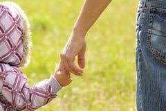 Il genitore tiene la mano di un bambino fotografie stock libere da diritti