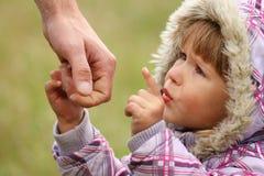 Il genitore tiene la mano di un bambino Immagine Stock