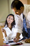 il gestore femminile nota gli introiti dell'ufficio che comunica l'operaio Immagini Stock