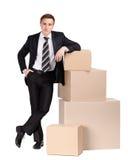 Il gestore si leva in piedi il mucchio vicino dei contenitori di pasteboard immagine stock