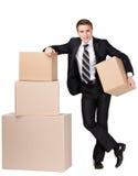 Il gestore si leva in piedi il mucchio vicino delle scatole di cartone Immagine Stock Libera da Diritti