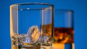 Il ghiaccio cade in un vetro e nell'altro vetro con la bevanda dell'oro su un fondo blu HD pieno, primo piano archivi video