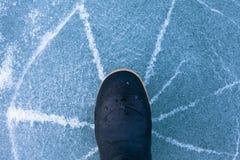 Il ghiaccio sottile del pericolo si fende radialmente sotto lo stivale di gomma fotografie stock libere da diritti