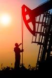 Il giacimento di petrolio, i lavoratori dell'olio sta funzionando Fotografie Stock Libere da Diritti
