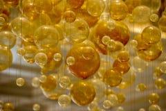 Il giallo bolle sfere di cristallo sospese in aria Immagini Stock