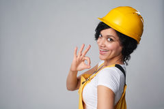 Il giallo d'uso del costruttore della donna protegge il casco ed il camice che mostrano OKAY Immagine Stock