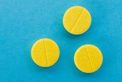 Il giallo riduce in pani le pillole su un fondo blu Fotografia Stock Libera da Diritti