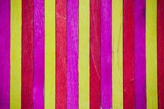 Il giallo vivo di rossi carmini colora il fondo di legno Immagini Stock