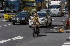 Il Giappone, Tokyo, 04/12/2017 Ciclista su una via della città immagini stock libere da diritti