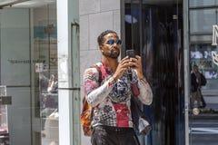 Il Giappone, Tokyo, 12 02 2017 Uomo di colore strutturato che prende le immagini su una via della città immagini stock
