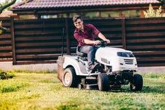 Il giardinaggio funziona con l'uomo che per mezzo della falciatrice da giardino, del trattore e degli strumenti di industriale Fotografia Stock