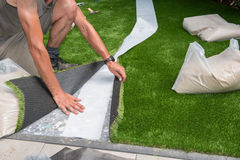 Il giardiniere professionista sta tagliando il tappeto erboso artificiale per adattarsi fotografia stock