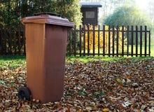 Il giardino con la pattumiera marrone per l'autunno caduto va Immagine Stock Libera da Diritti