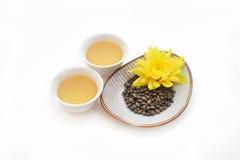 Il ginseng ha torto le foglie di tè con il fiore giallo e due tazze di tè Fotografie Stock Libere da Diritti