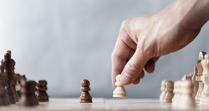 Il giocatore del gioco di scacchi rende ad un movimento il pegno bianco un passo avanti fotografia stock