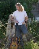 Il giocatore di chitarra con indicatore luminoso dietro Immagine Stock