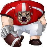 Il giocatore di football americano bianco rosso si inginocchia e tiene la palla Fotografia Stock