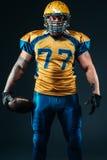 Il giocatore di football americano tiene la palla in mani immagine stock libera da diritti