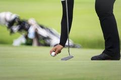Il giocatore di golf femminile segna la sua posizione della palla su un verde Immagine Stock