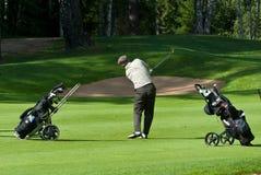 Il giocatore di golf rifinisce la sua oscillazione Fotografia Stock