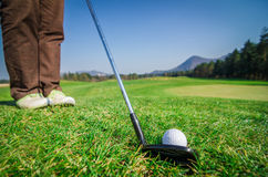 Il giocatore di golf sta scheggiando una palla da golf sul verde con il golf c del driver Fotografia Stock
