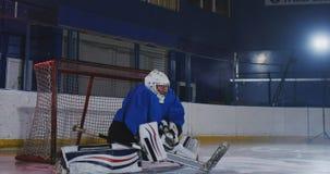 Il giocatore di hockey conduce un attacco allo scopo dell'oppositore Trovandosi in un casco prende il disco e conserva la partita stock footage