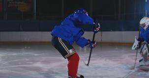 Il giocatore di hockey conduce un attacco allo scopo dell'oppositore Trovandosi in un casco prende il disco e conserva la partita video d archivio