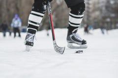 Il giocatore di hockey funziona con il disco sul ghiaccio immagini stock libere da diritti