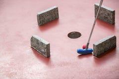 Il giocatore di Minigolf colpisce un wihtin della palla una matrice degli ostacoli ad un MI Fotografie Stock Libere da Diritti