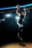 Il giocatore di pallacanestro nell'azione spara una palla nell'anello Fotografia Stock Libera da Diritti