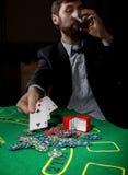 Il giocatore di poker che mostra una combinazione perdente nelle carte di un poker, uomo beve il whiskey dal dolore Fotografia Stock