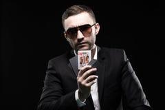 Il giocatore di poker in vetri neri, in un casinò con l'una carta aperta su un fondo nero Fotografie Stock Libere da Diritti