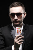 Il giocatore di poker in vetri neri, in un casinò con l'una carta aperta su un fondo nero Immagine Stock Libera da Diritti