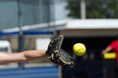 Il giocatore di softball raggiunge fuori per prendere la palla Immagini Stock