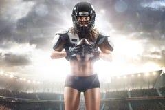Il giocatore femminile di football americano sta posando Fotografia Stock