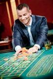 Il giocatore picchetta il mucchio dei chip al casinò Fotografia Stock Libera da Diritti