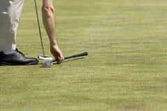 Il giocatore prende un azionamento su un terreno da golf verde Immagini Stock Libere da Diritti