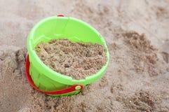 Il giocattolo del secchio dei bambini con la sabbia Fotografia Stock Libera da Diritti