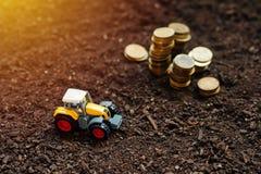 Il giocattolo del trattore agricolo e le monete dorate su suolo fertile atterrano Immagine Stock