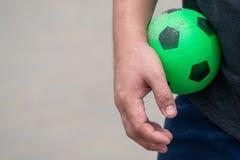 Il giocattolo di gomma verde di calcio è stato tenuto nella mano del maschio fotografia stock