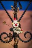 Il giocattolo trascurato del pagliaccio sul recinto con la decomposizione fiorisce Fotografia Stock Libera da Diritti