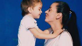 Il gioco del figlio e della madre ride e bacia su un fondo blu archivi video